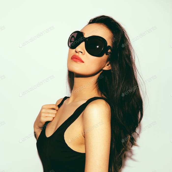 Brunette model in stylish sunglasses. Summer beach vibes