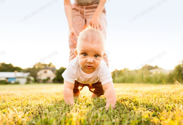 Baby boy with unrecognizable mother crawling outside.