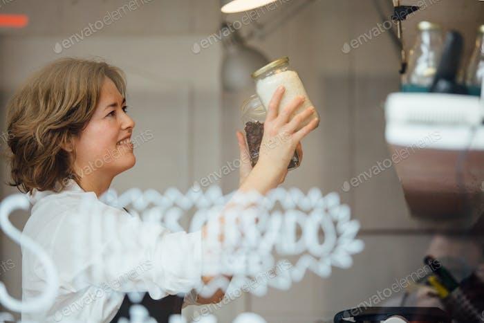 Woman putting jars on shelf