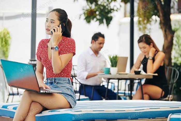 Junge Frau mit Laptop telefonieren