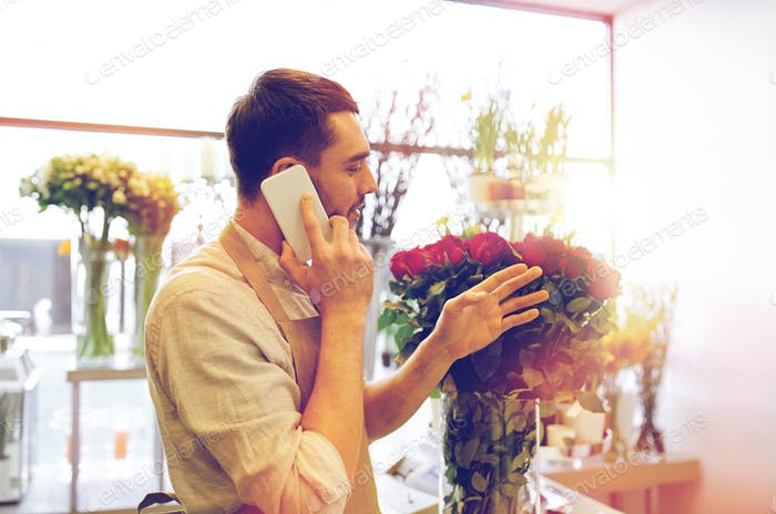 man with smartphone and red roses at flower shop