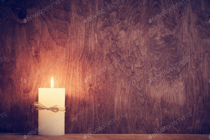 Chistmas candle glowing on wooden wall background.