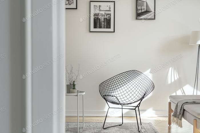 Industrial chair on the middle of black and white interior with photos on the wall