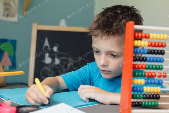 Schoolboy working on math homework with an abacus