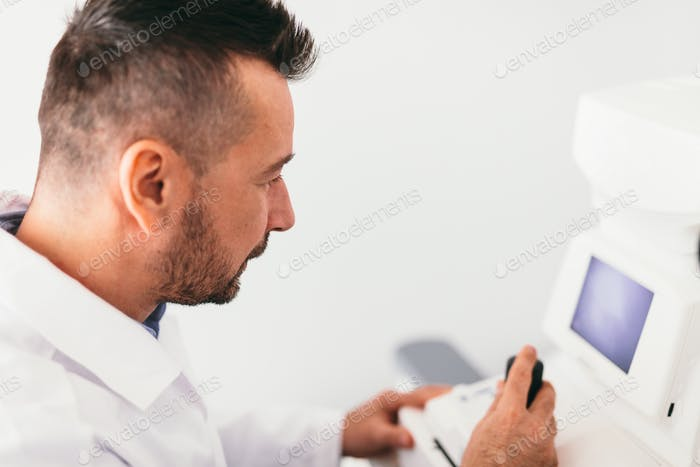 Optician examining patient's eye on a machine.
