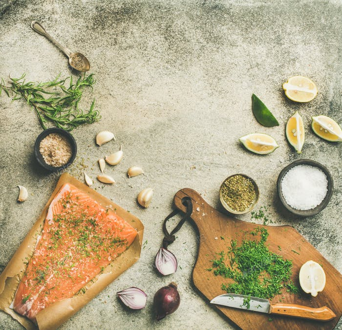 Cooking salted salmon fish with herbs and salts, copy space