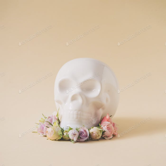 White skull with pink and purple spring flowers. Minimal love concept. Creative season idea.