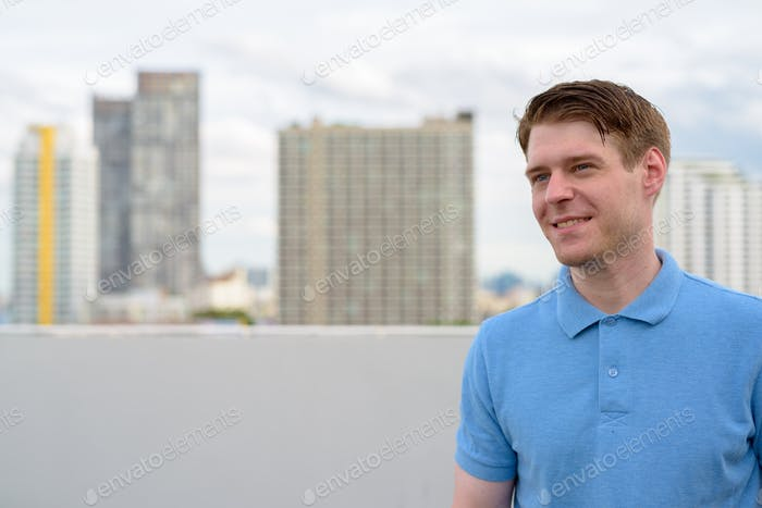 Young handsome man thinking against view of the city