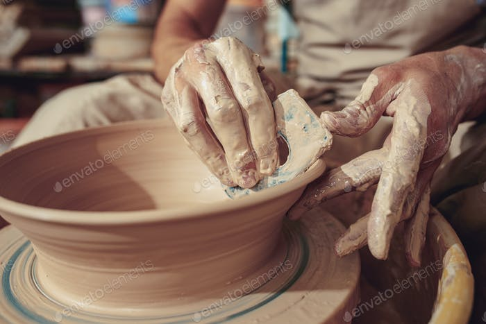 Creating a jar or vase of white clay close-up. Master crock. Man hands making clay jug macro.