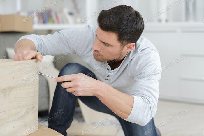 Mann Montage Möbel zu Hause auf dem Boden