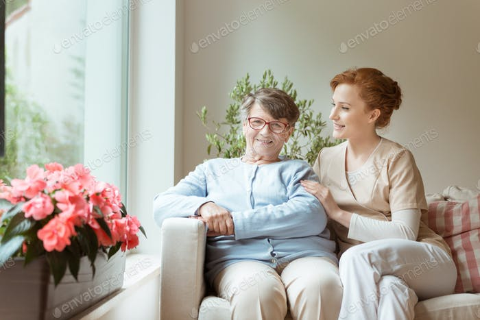 A senior woman with a medical support professional sitting on a