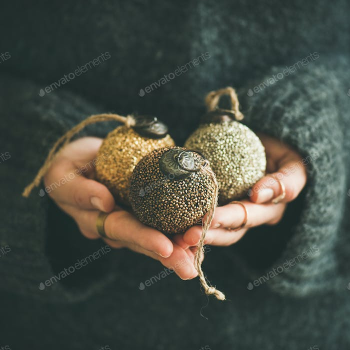 Woman holding golden and silver balls in hands, square crop