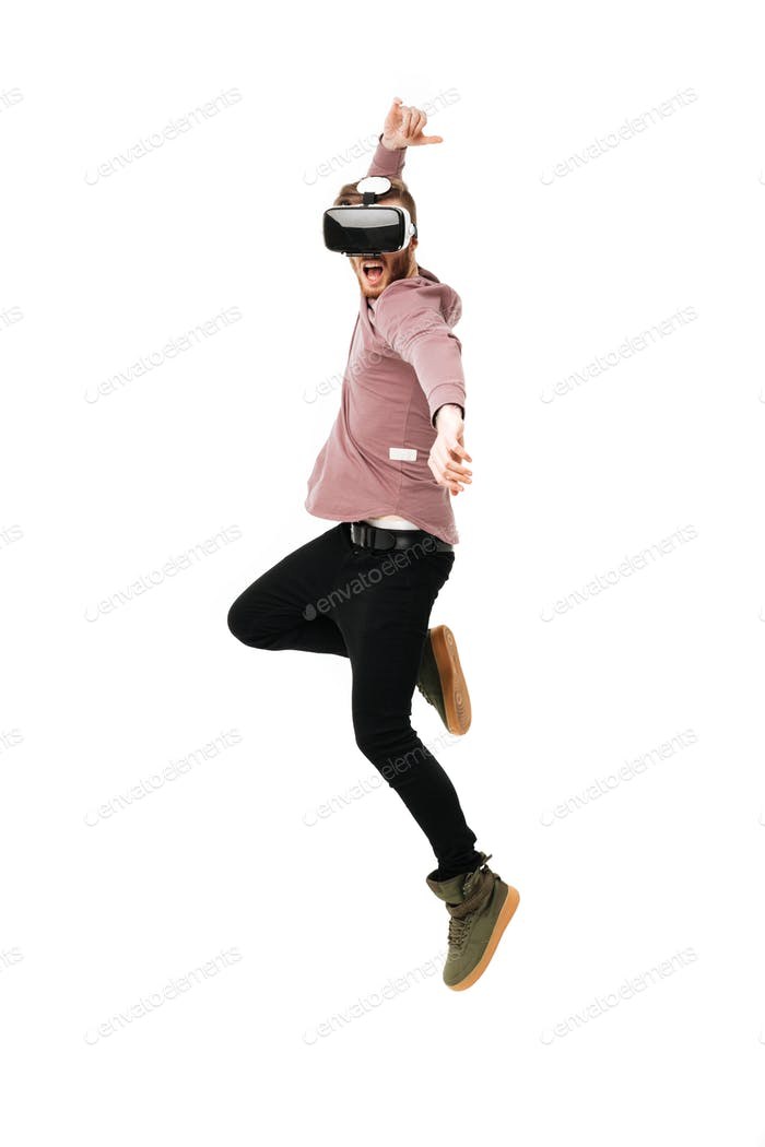 Young emotional man fighting and jumping in virtual reality glasses over white background