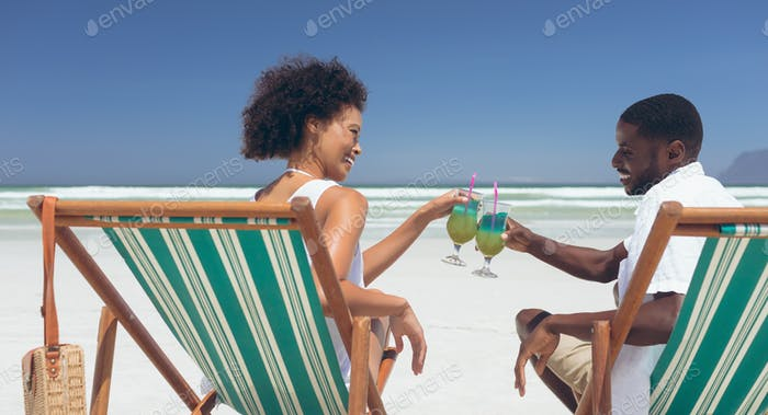 Young couple relaxing on sun lounger at beach in a sunny day