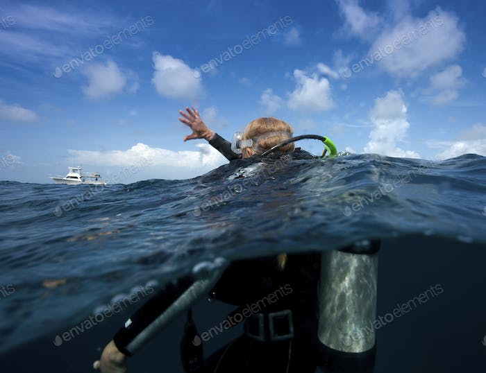 Scuba diver waves one arm to show distress and that she requires assistance.