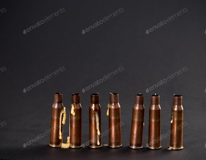 Empty rifle cartridges with melted candles.