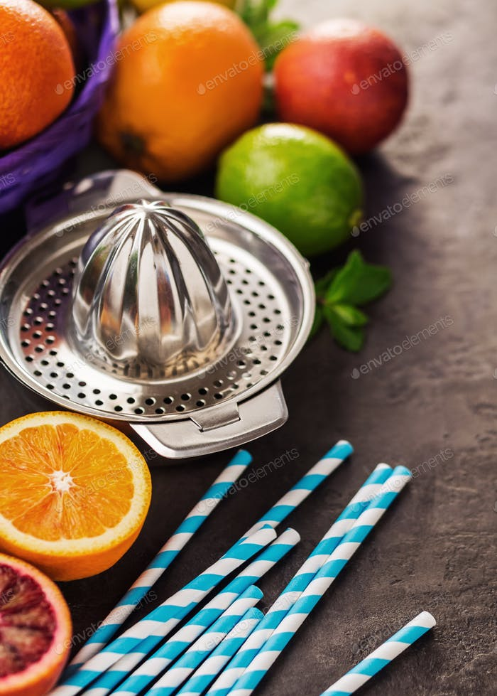 Juicer with different citrus fruits, oranges, limes and lemons.