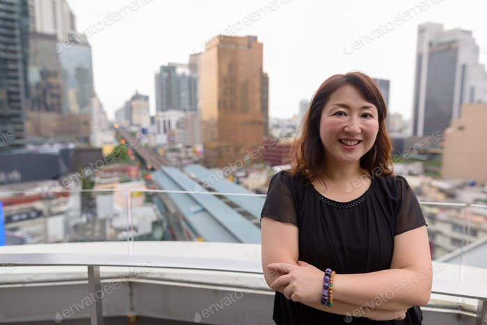 Mature beautiful Asian woman against view of the city