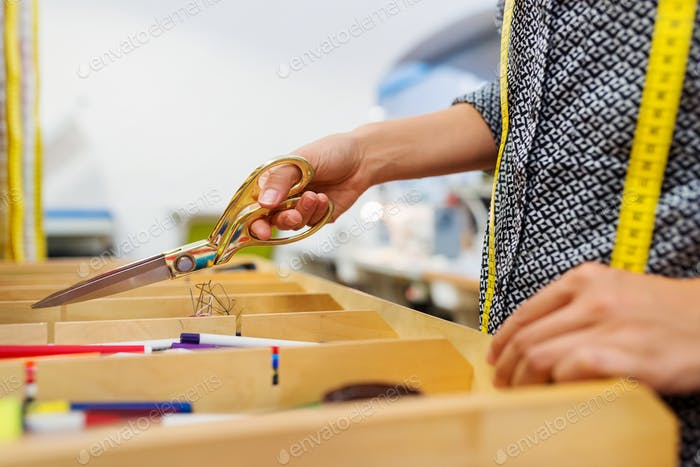 Unrecognizable tailor woman taking scissors out of a drawer