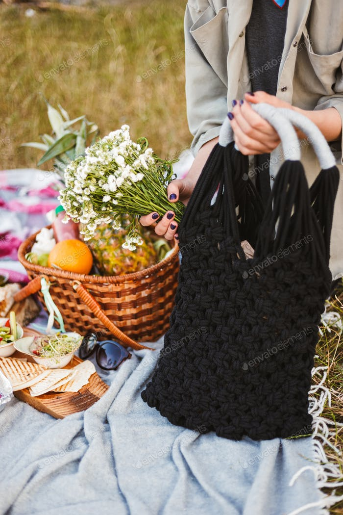 Close up photo of woman hands holding black bag and wildflowers