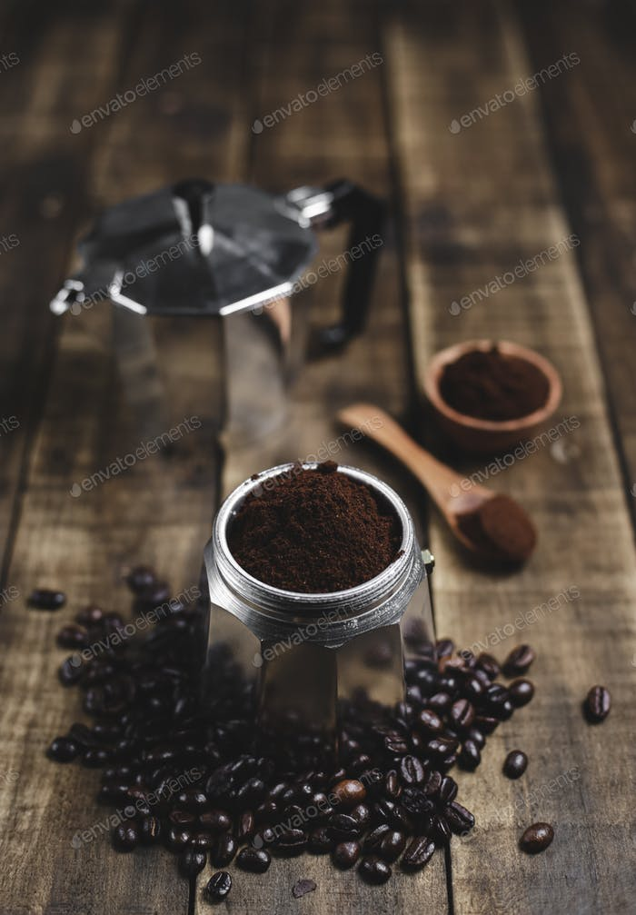 ground coffee and moka pot on wood background