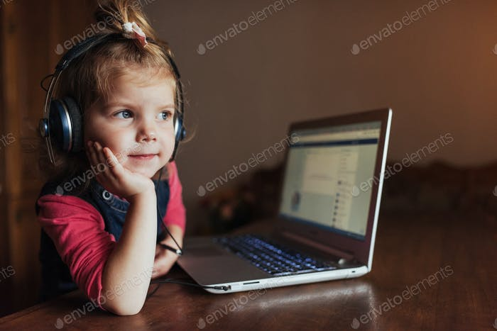 little girl with headphones listening to music, using laptop
