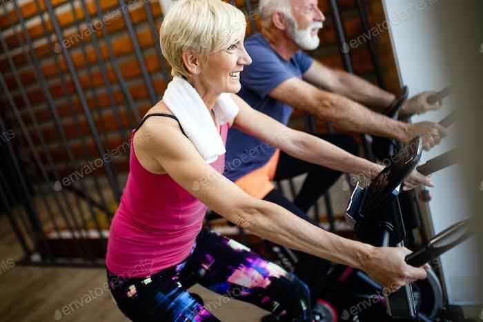 Reife fit Menschen Radfahren in der Turnhalle, Training Beine tun Cardio Workout Radfahren Fahrrad