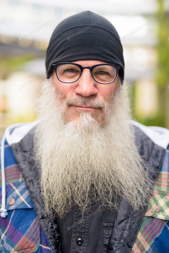 Mature handsome bearded hipster man with eyeglasses outdoors