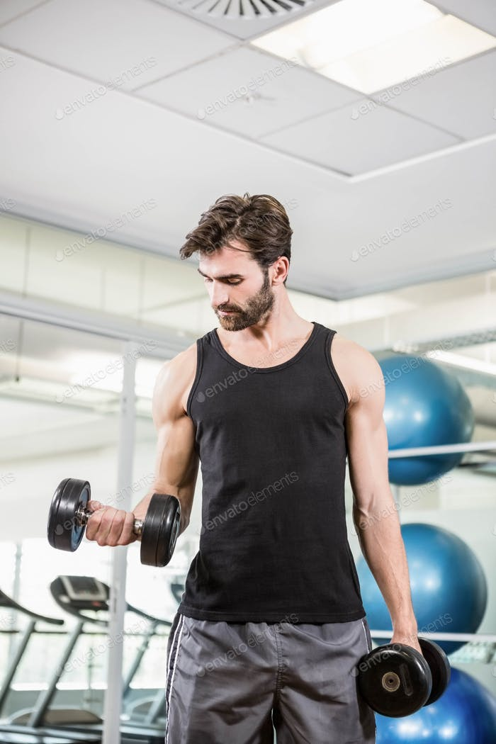 Concentrated man lifting dumbbells in the studio