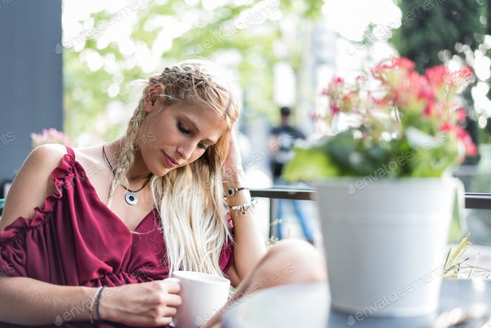 Beautiful blonde woman drinking a cup of coffee in a terrace