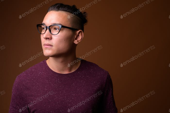 Young handsome multi-ethnic man against brown background