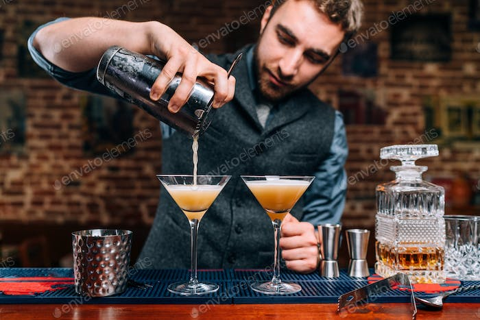 Close up details of barman pouring fancy alcoholic drinks at party