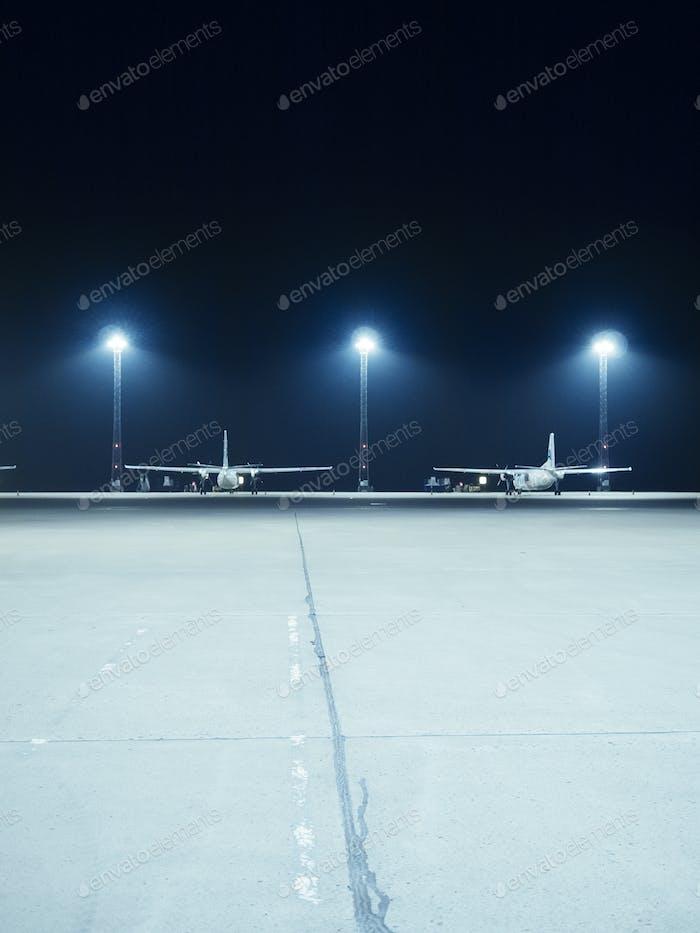 Beleuchtete Flutlichter vor Flugzeugen, die am Terminal abgestellt sind