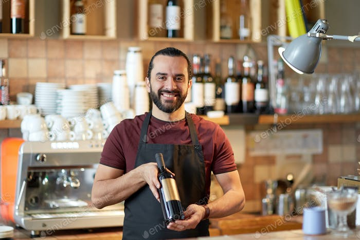 happy man or waiter with bottle of red wine at bar
