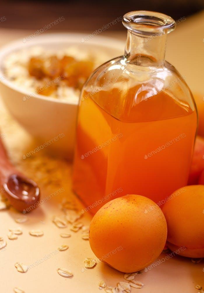 Gesundes Frühstück. Weiße Platte Haferflocken mit getrockneten Aprikosen, ein Glas Aprikosensaft