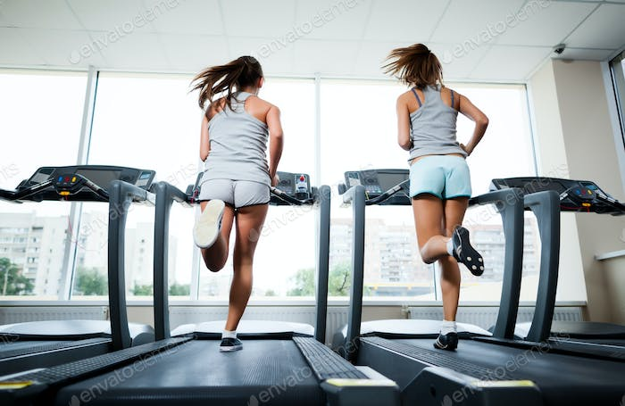 Two young beautiful slim women in sportswear running on treadmills in gym with windows and city at