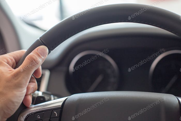 Male hand holding a car steering wheel