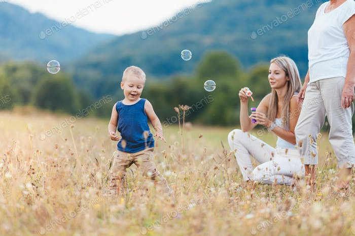 Happy child with family having a great time blowing bubbles