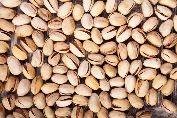 Thumbnail for Over top close up view of Pistachios on wooden background in stu