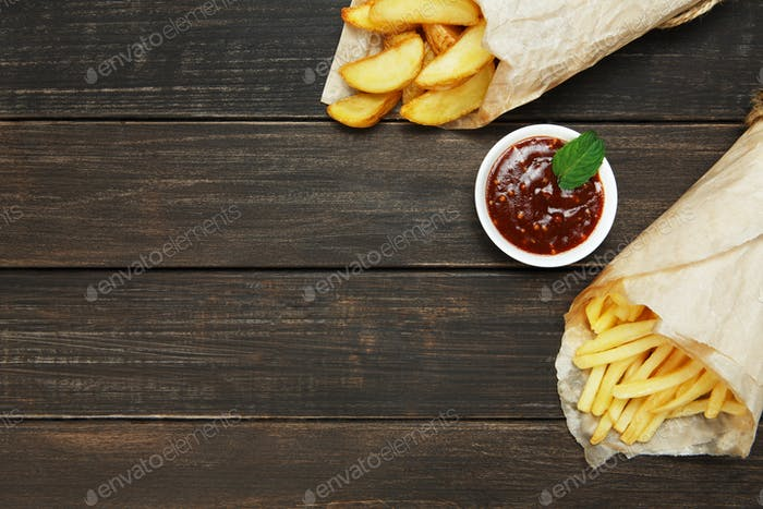 Fries and potato wedges wrapped takeaway at wood