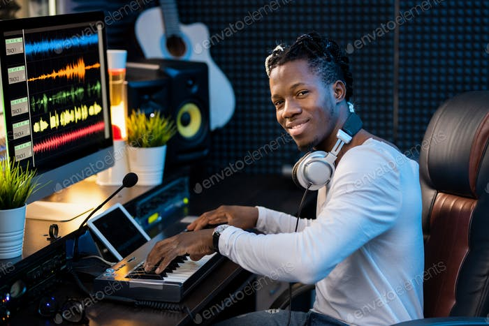 Happy young musician with headphones on neck working over new music by workplace