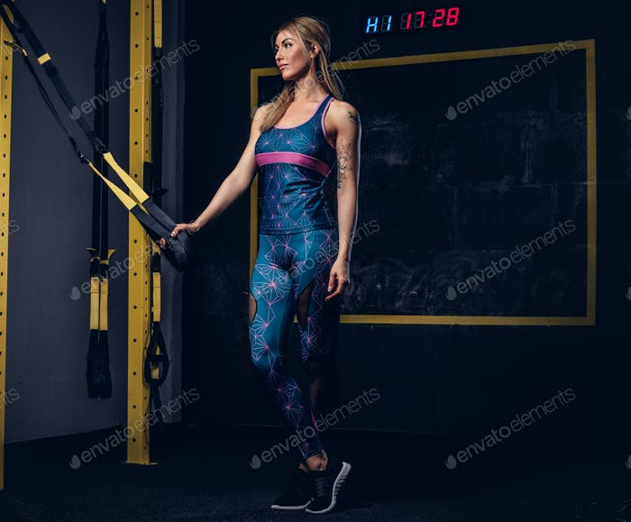 Beautiful fit woman in sportswear doing exercise with suspension straps system at gym.