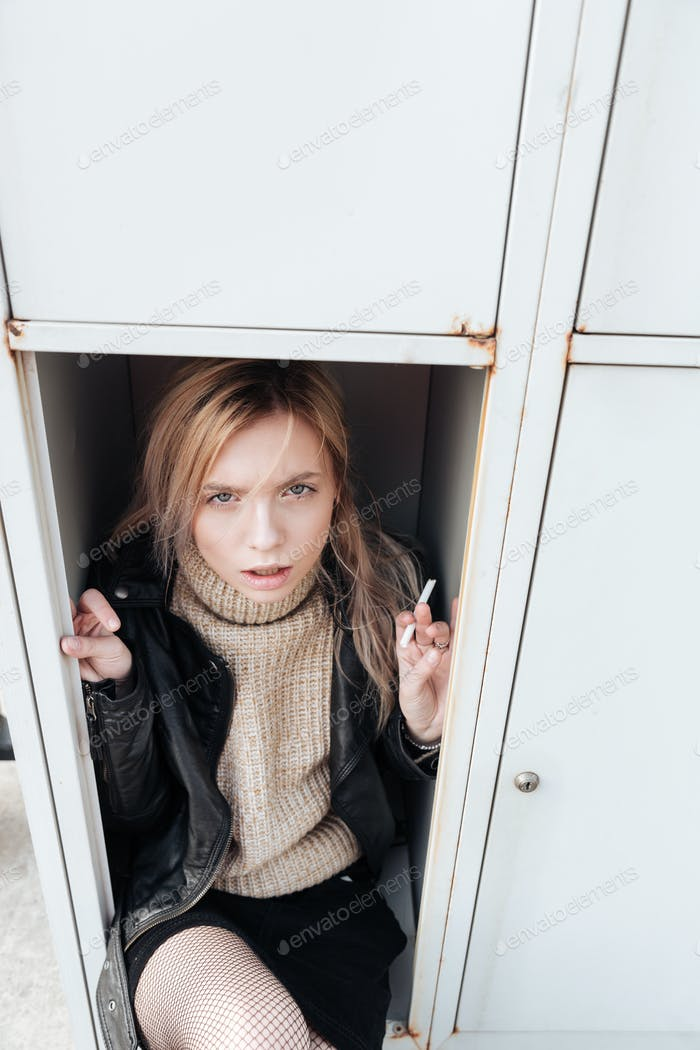 Serious young blonde lady sitting in safe