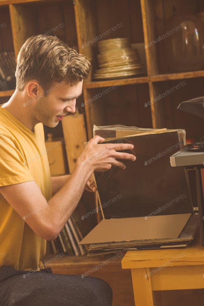 Young man looking at his vinyl collection at home in the living room