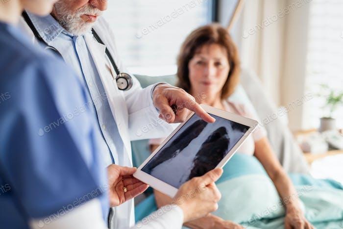 Senior männlicher Arzt untersucht eine Frau Patientin im Krankenhaus, überprüft Röntgenaufnahme.
