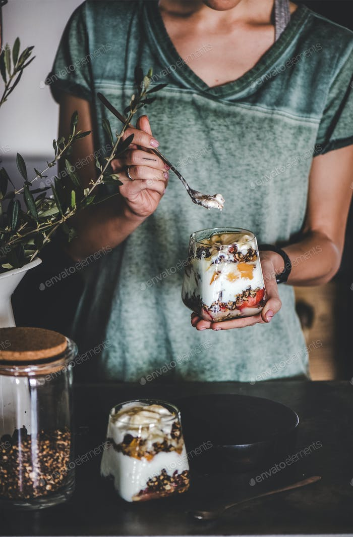 Frau mit gesundem veganem Frühstück mit Joghurt im Glas
