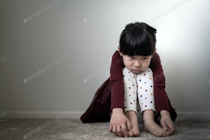 Lonely sad little girl holding her knees
