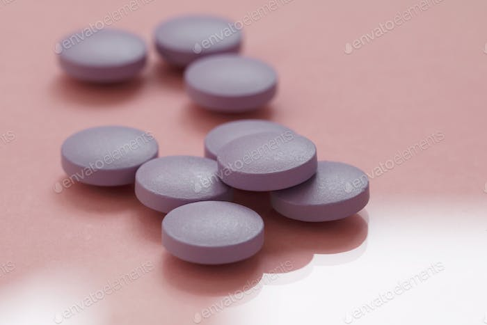Close-up of purple pills on a pink background.