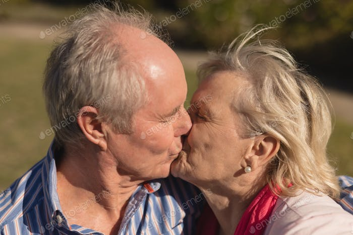 Front view of active senior Caucasian couple kissing each other in the park