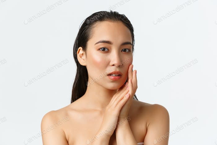 Skincare, bodycare, beauty and bath concept. Sensual beautiful asian woman standing naked, touching